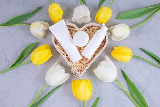 Recipientes de frascos de cosméticos brancos em uma caixa de madeira ao redor de flores de tulipas
