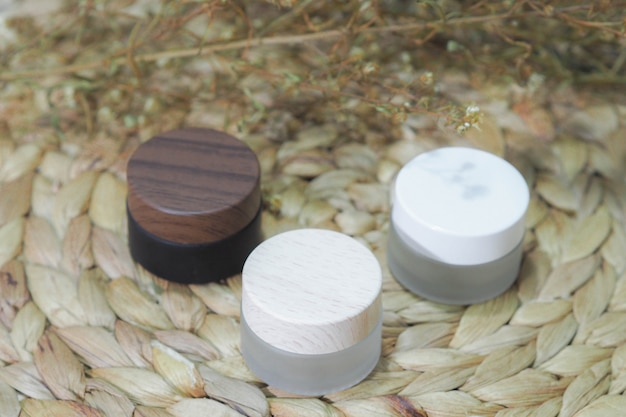 Recipientes de garrafa cosméticos branco, marrom, produto de creme com flor seca.