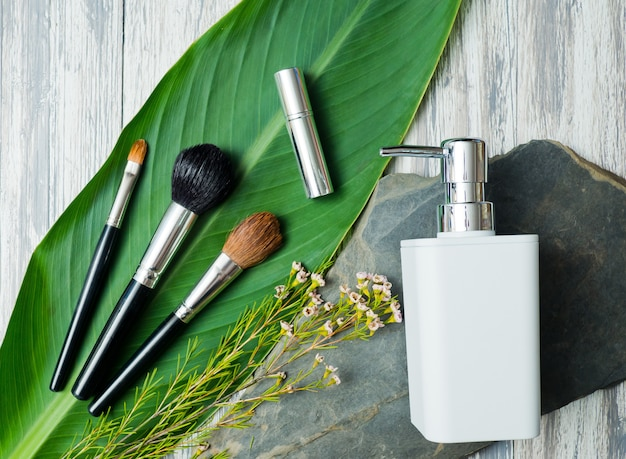 Recipientes de garrafa de cosméticos naturais no fundo da folha verde