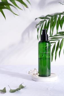 Recipientes de garrafa verde cosmético com sombra tropical da folha, modelo de marcagem com ferro quente, conceito de produto natural da beleza.