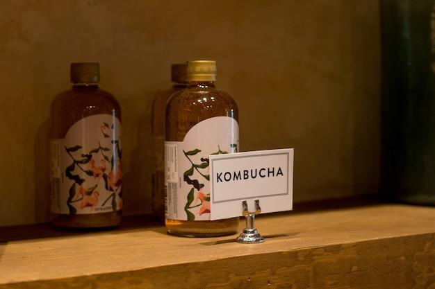 Recipientes de kombuchá sobre balcão, com etiqueta.