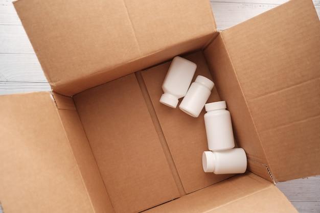 Recipientes de pílulas médicas abertas em uma caixa