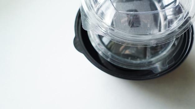 Recipientes de plástico preto e branco para alimentos em fundo branco