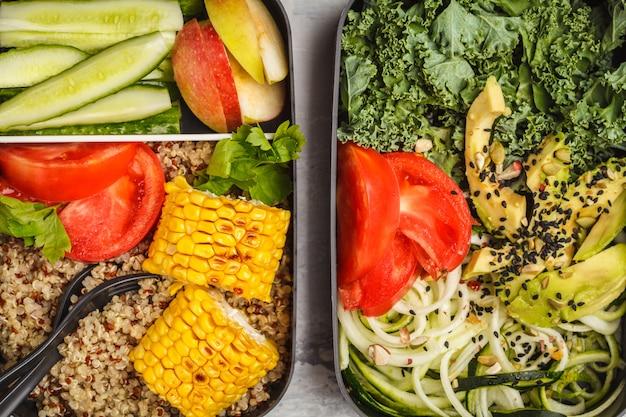 Recipientes de preparação de refeição saudável com quinoa, abacate, milho, macarrão de abobrinha e couve. comida para viagem.