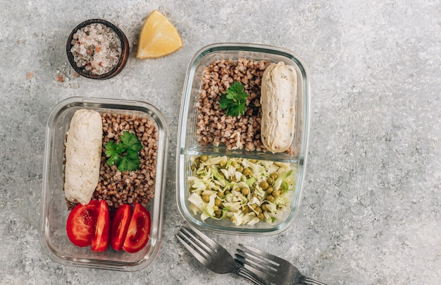 Recipientes de preparação de refeição saudável com salsichas de frango caseiras, trigo sarraceno e salada de legumes em fundo de pedra.