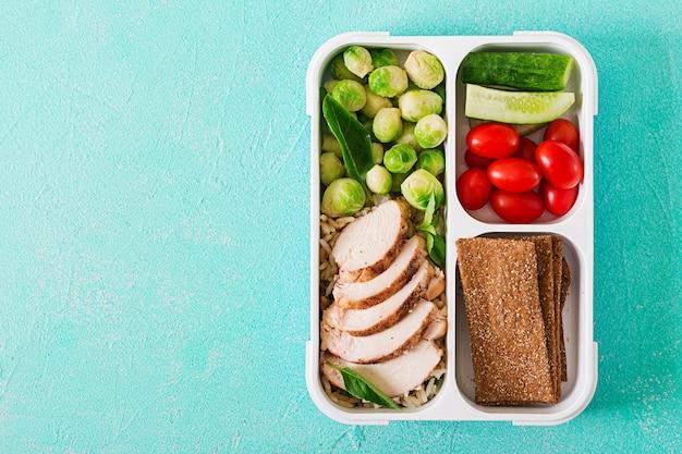 Recipientes de preparação de refeição verde saudável com filé de frango, arroz, couve de bruxelas e legumes
