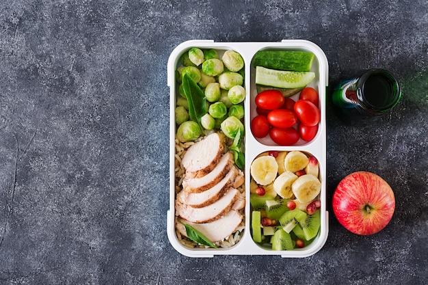 Recipientes de preparação de refeição verde saudável com filé de frango, arroz, couve de bruxelas, legumes e frutas