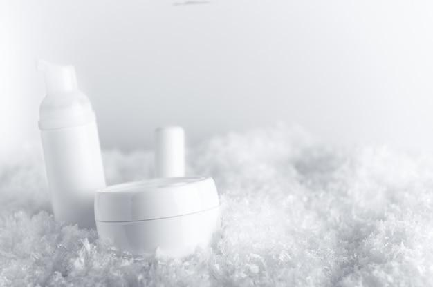 Recipientes de produtos cosméticos na neve fofa branca.