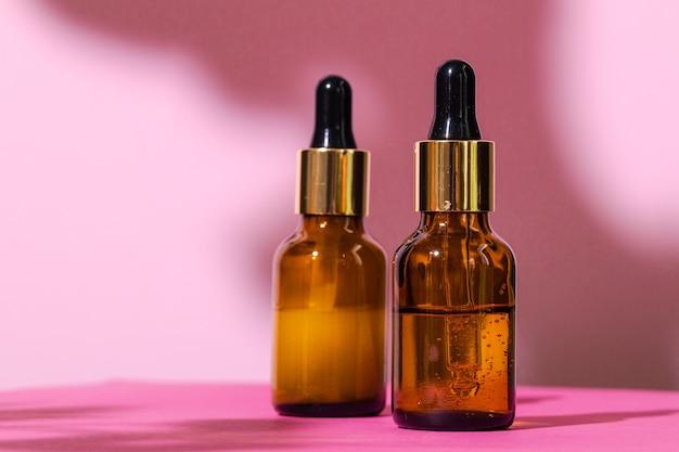Recipientes de produtos para a pele em fundo rosa brilhante close-up