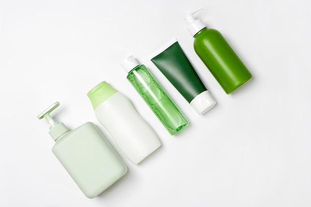 Recipientes de tamanho e formas diferentes para condicionador de tônico de toner limpador, sabonete e xampu em fundo branco. produtos de beleza orgânicos naturais