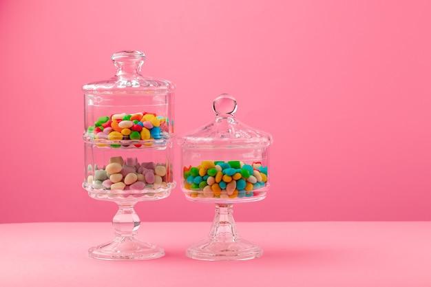 Recipientes de vidro com doces em um fundo rosa