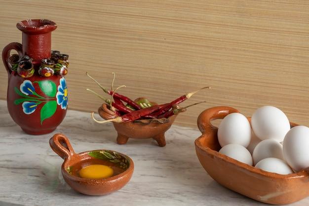 Recipientes mexicanos típicos com ingredientes como ovo chili peppers e água