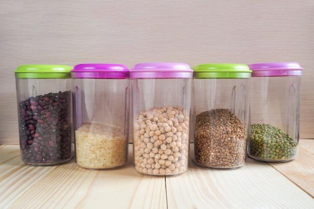 Recipientes plásticos com cereais. produtos de armazenamento doméstico.
