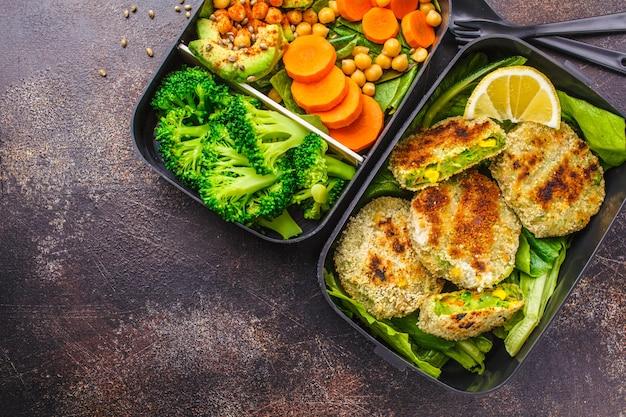 Recipientes saudáveis da preparação da refeição com hamburgueres, brócolis, grãos-de-bico e salada verdes.