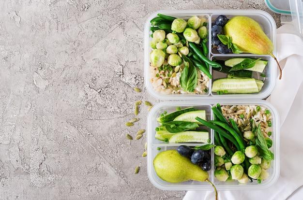 Recipientes veganos de preparação de refeições verdes com arroz, feijão verde, couve de bruxelas, pepino e frutas. jantar na lancheira. vista do topo. configuração plana