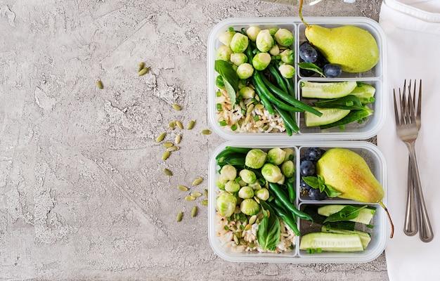 Recipientes veganos de preparação de refeições verdes com arroz, feijão verde, couve de bruxelas, pepino e frutas. jantar na lancheira.