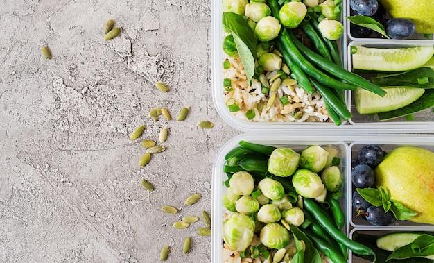 Recipientes veganos de preparação de refeições verdes com arroz, feijão verde, couve de bruxelas, pepino e frutas.