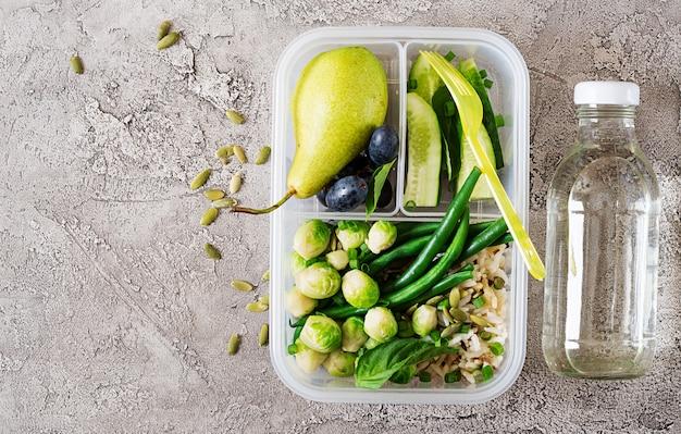 Recipientes verdes da preparação da refeição do vegetariano com arroz, os feijões verdes, as couves-de-bruxelas, o pepino e os frutos.