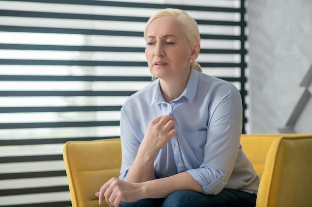 Reclamações, saúde. triste mulher adulta com cabelos loiros, sentado em uma cadeira perto da janela, falando na testa franzindo a testa.