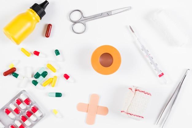 Recolha de garrafa médica; pílulas; bandagem e termômetro isolado no fundo branco
