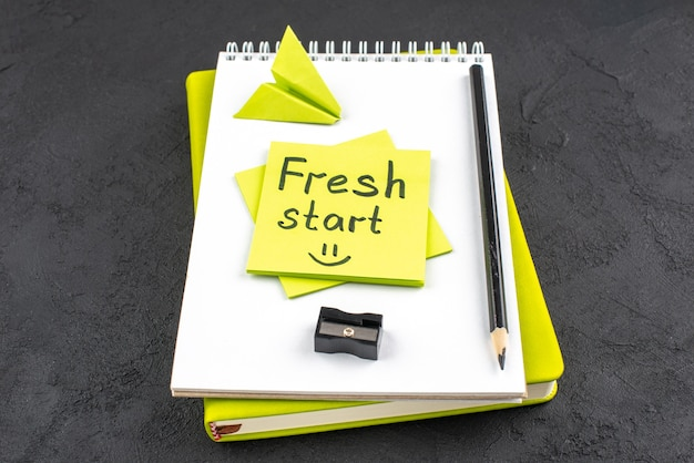 Recomeço da vista inferior escrito em nota adesiva amarela no bloco de notas, lápis preto e apontador de lápis em fundo escuro