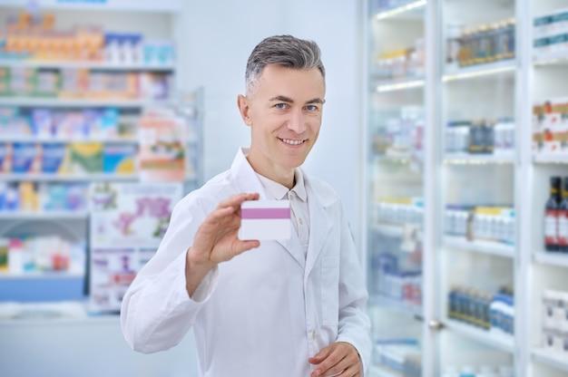 Recomendação. homem adulto de jaleco branco sorrindo com otimismo e mostrando medicamento em pé perto de prateleiras com remédios na farmácia
