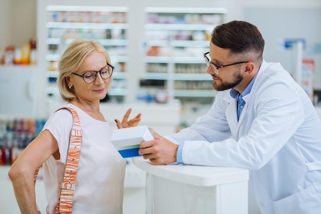 Recomendação profissional. mulher encantada de pé em semi-posição e olhando a embalagem com comprimidos