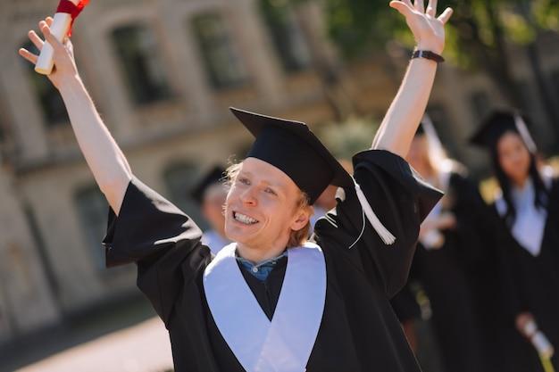 Recompensa desejada. menino feliz e sorridente, levantando as mãos com o diploma enrolado no ar após sua cerimônia de formatura no quintal.