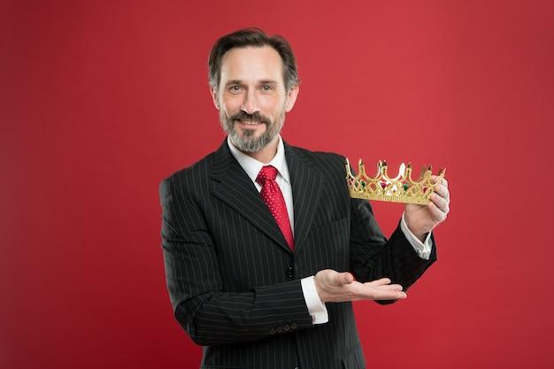 Recompensa rica. empresário maduro mostrando a recompensa da coroa sobre fundo vermelho. o chefão da successfil premia o vencedor com uma recompensa preciosa pelo sucesso. ganhando prêmio e recompensa valiosos.
