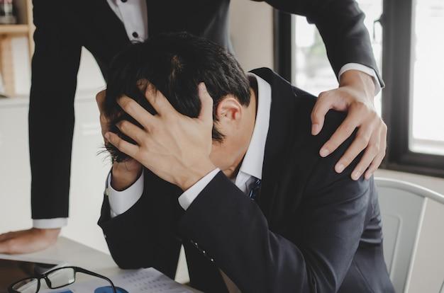 Reconfortante. homem de negócios asiáticos chateado com problemas com o apoio de seu amigo e sentado no escritório em casa