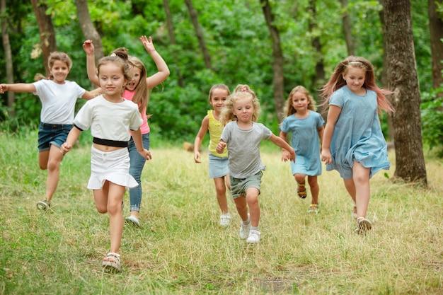 Recordações. crianças, crianças correndo na floresta verde.