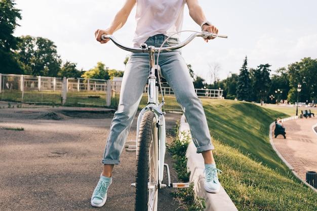 Recortado, imagem, de, um, mulher, em, calças brim, e, um, t-shirt, sentando, ligado, um, bicicleta cidade, em, um, parque
