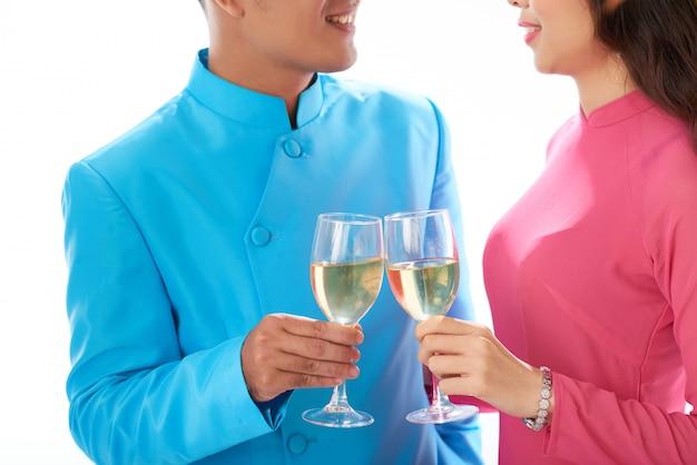 Recortado, par asiático, em, roupa tradicional, desfrutando vinho