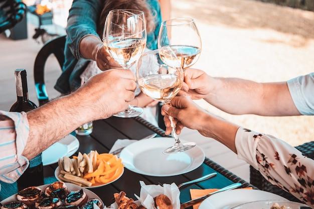 Recortar foto de close-up das mãos do grupo de amigos no pátio sobre um copo de vinho branco.
