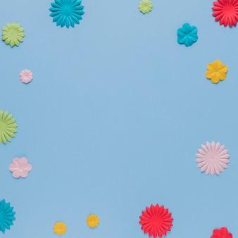 Recorte de flores origami colorido sobre fundo azul