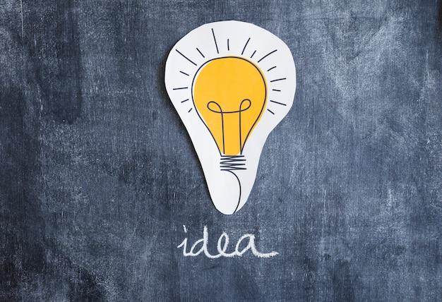 Recorte de papel lâmpada com texto de idéia na lousa