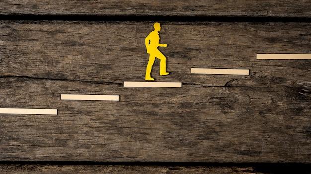 Recorte de silhueta amarela de uma pessoa subindo as escadas sobre madeira rústica em direção à carreira.