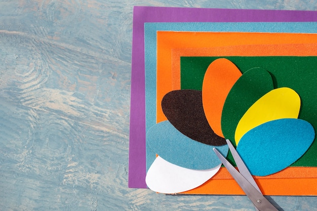 Recorte ovos de papel de páscoa coloridos, padrão e tesoura em papel colorido em uma mesa de madeira azul, copie o espaço, vista superior, postura plana. artesanato de papel criativo diy para a páscoa.