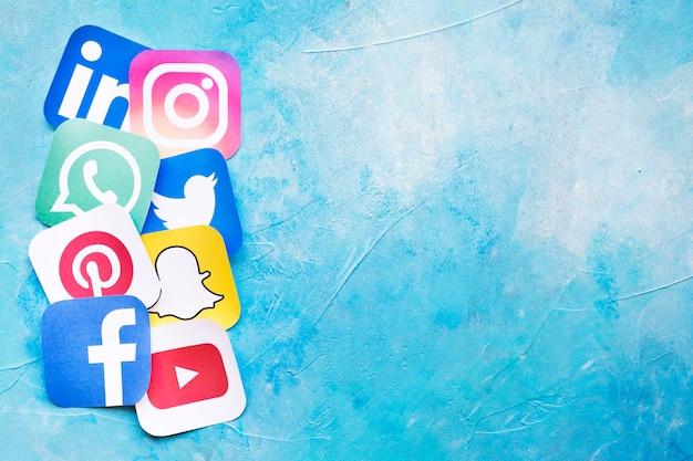 Recortes de papel de ícones de redes sociais sobre o pano de fundo azul