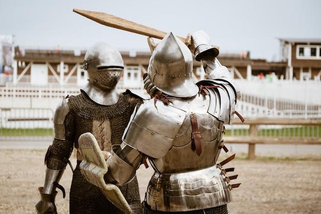 Recriação da batalha de cavaleiros medievais em armaduras pesadas e espadas de madeira