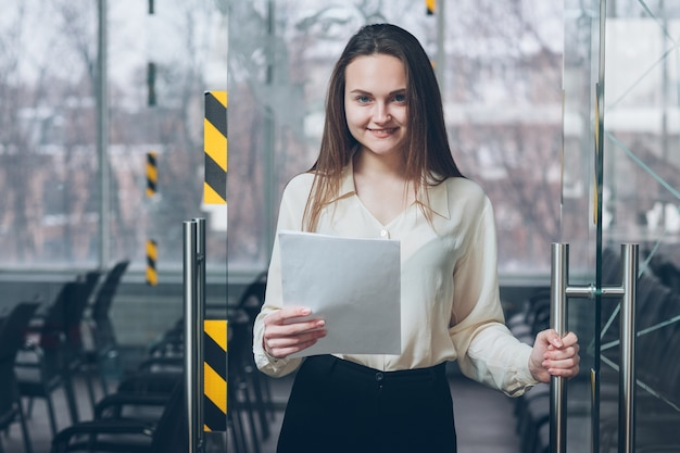 Recrutador de empregos. bem-vindo ao trabalho. mulher jovem sorridente abrindo a porta do escritório de negócios com documentos nas mãos.