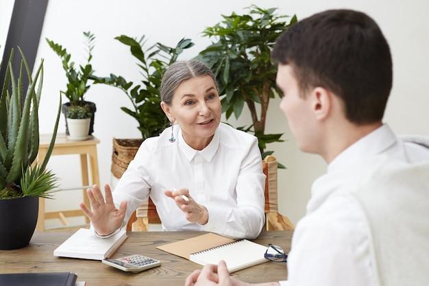 Recrutador de mulher sênior bem-sucedido em camisa branca, sentado em seu local de trabalho e entrevistando o candidato a emprego irreconhecível de homem. dois colegas do sexo masculino e feminino discutindo negócios em um escritório moderno