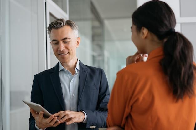 Recrutador maduro usando o currículo de leitura do tablet digital, ouvindo o candidato na entrevista de emprego.