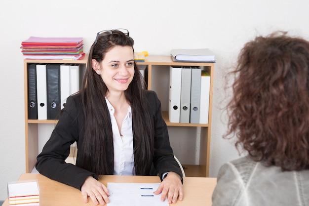 Recrutador qualificado da mulher que faz a entrevista de emprego com a fêmea para a ocupação que lê o papel cv