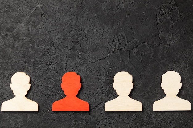 Recrutamento de pessoal. as figuras dos trabalhadores são todas iguais e uma em vermelho. escolha do líder. rh fundo preto. copie o espaço para o texto.