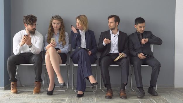 Recrutamento para a empresa. jovens candidatos aguardam entrevista. um grupo de jovens entediado esperando a entrevista de emprego.