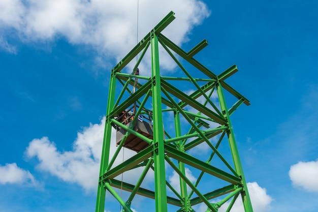 Recursos humanos que instalam o suporte da estrutura de aço para o equipamento no canteiro de obras.