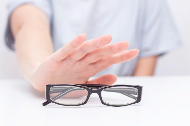 Recusa de óculos à vista. mãos recusam óculos. cruz em copos. melhoria da visão, correção da visão a laser.