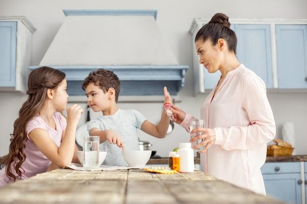 Recusa. menino bonito e irritado de cabelos escuros tomando café da manhã com sua irmã e se recusando a tomar vitaminas que sua mãe estava dando a ele