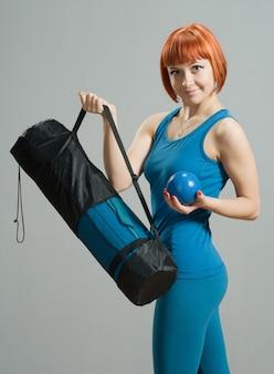 Red-haired fitness girl com esteira de ioga